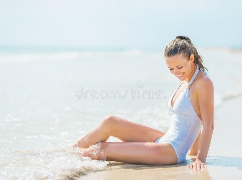 Szczęśliwa młoda kobieta w swimsuit cieszy się siedzieć w wodzie morskiej fotografia stock