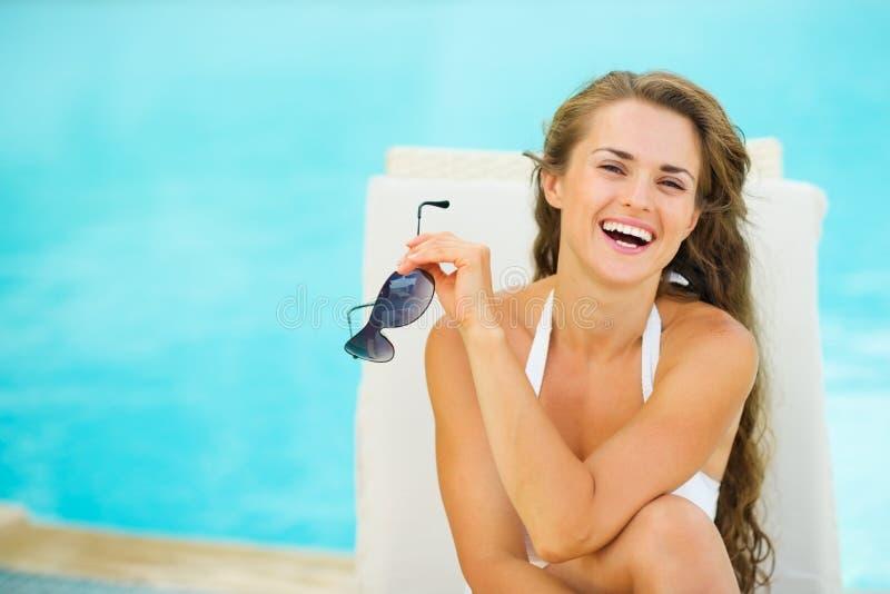 Szczęśliwa młoda kobieta w swimsuit relaksującym poolside obraz stock