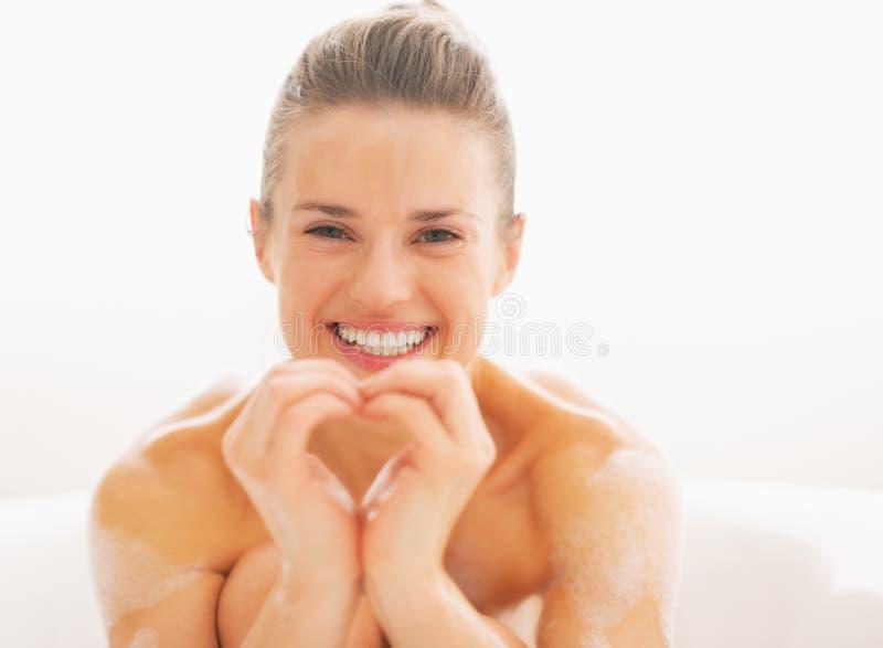 Szczęśliwa młoda kobieta w wannie pokazuje serce z rękami zdjęcia stock