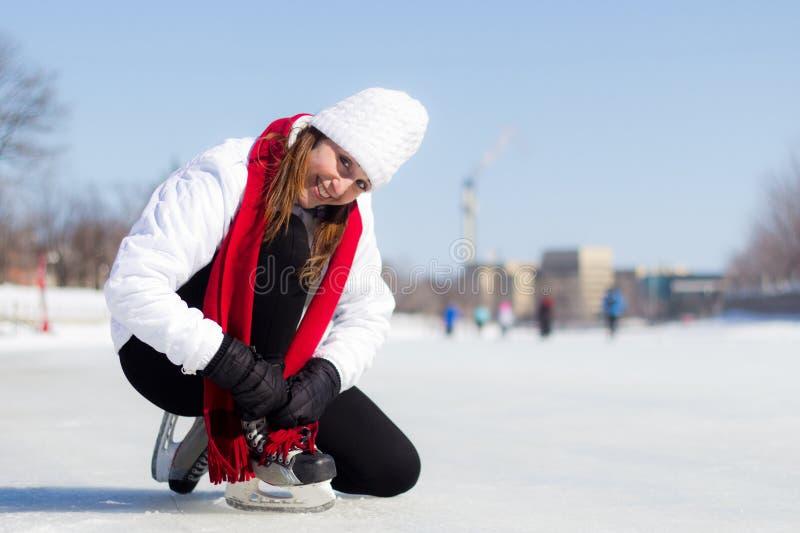 Szczęśliwa młoda kobieta wiąże jej lodowe łyżwy w zimie fotografia royalty free
