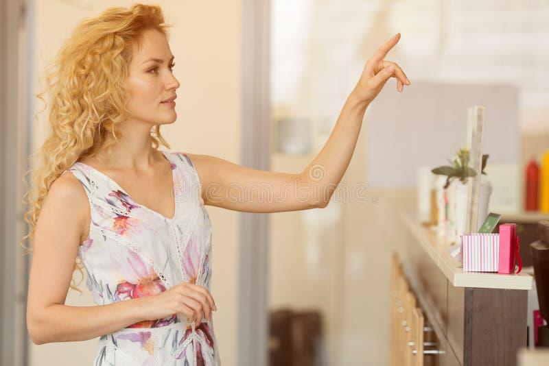 Szczęśliwa młoda kobieta wybiera świetne czekolady i ciasteczko przy kawiarnią obrazy stock