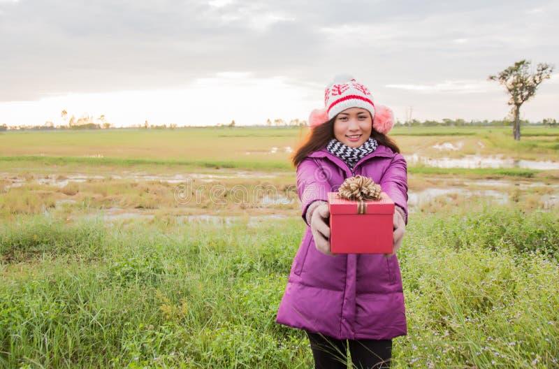 Szczęśliwa młoda kobieta z darem w rękach Koncepcja świąteczna i zimowa fotografia stock