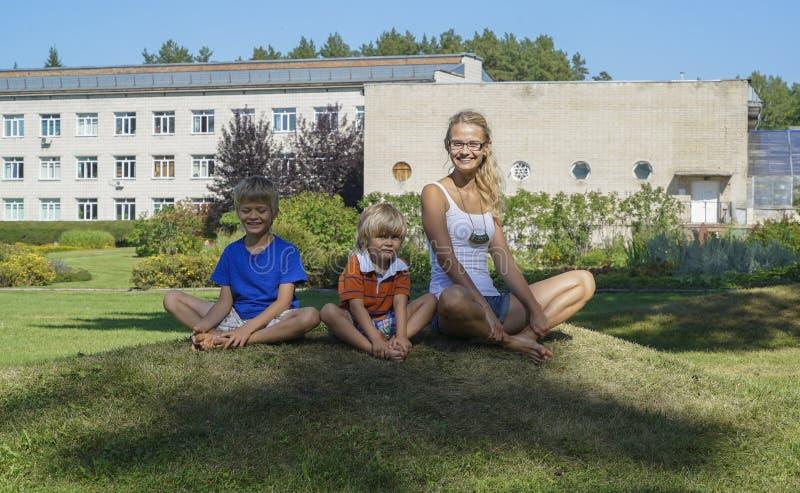 Szczęśliwa młoda kobieta z dwa chłopiec ćwiczy joga zdjęcia royalty free