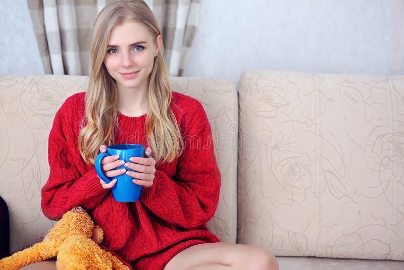 Szczęśliwa młoda kobieta z filiżanką herbaciany lub kawowy obsiadanie na kanapie w domu Napoje i czasu wolnego pojęcie - zdjęcia stock