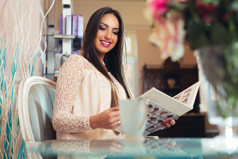 Szczęśliwa młoda kobieta z fryzjerem wybiera włosianego kolor od palet próbek przy salonem fotografia royalty free
