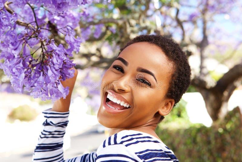 Szczęśliwa młoda kobieta z kwiatem na drzewie zdjęcie stock