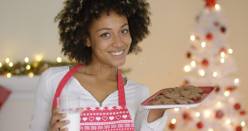 Szczęśliwa młoda kobieta z mlekiem i ciastkami dla Santa zdjęcie stock