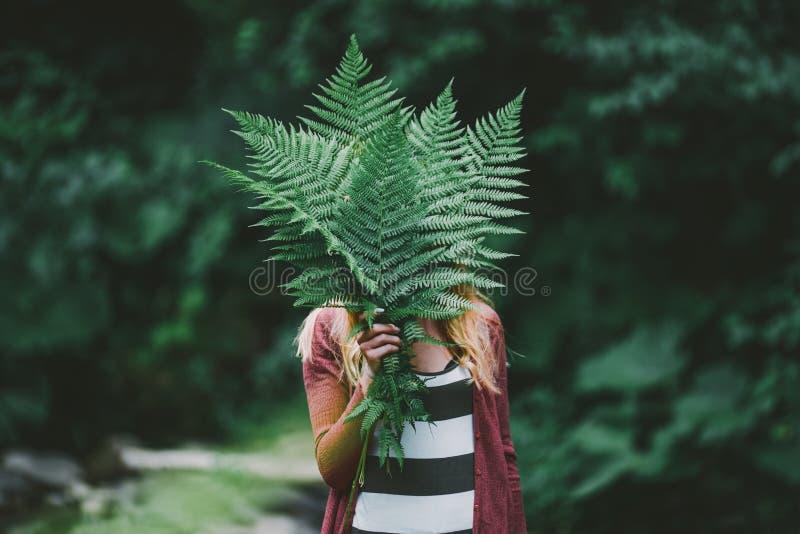 Szczęśliwa młoda kobieta z paprociowym liściem w zielonej naturze, zdjęcie royalty free