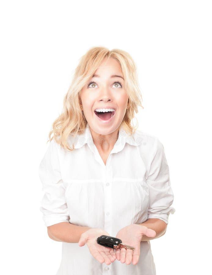 Szczęśliwa młoda kobieta z samochodu kluczem na biel. obraz stock
