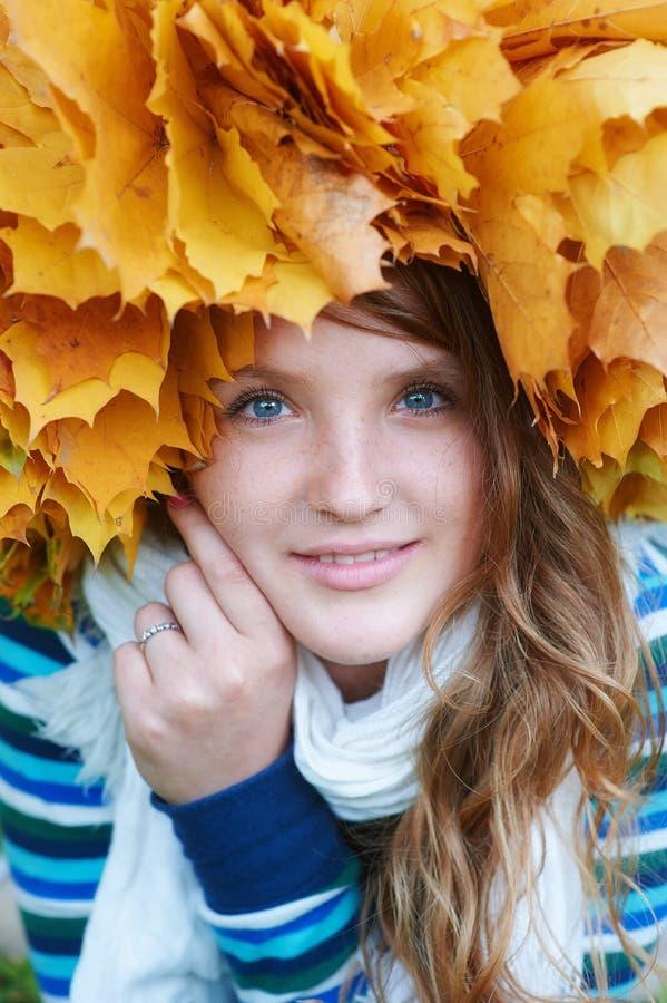 Szczęśliwa młoda kobieta z wiankiem kolor żółty opuszcza odprowadzenie w parku zdjęcie stock