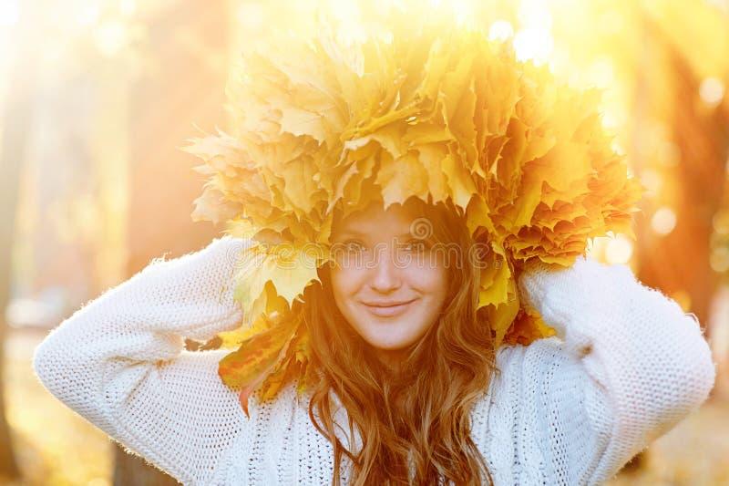 Szczęśliwa młoda kobieta z wiankiem kolor żółty opuszcza odprowadzenie w parku zdjęcie royalty free