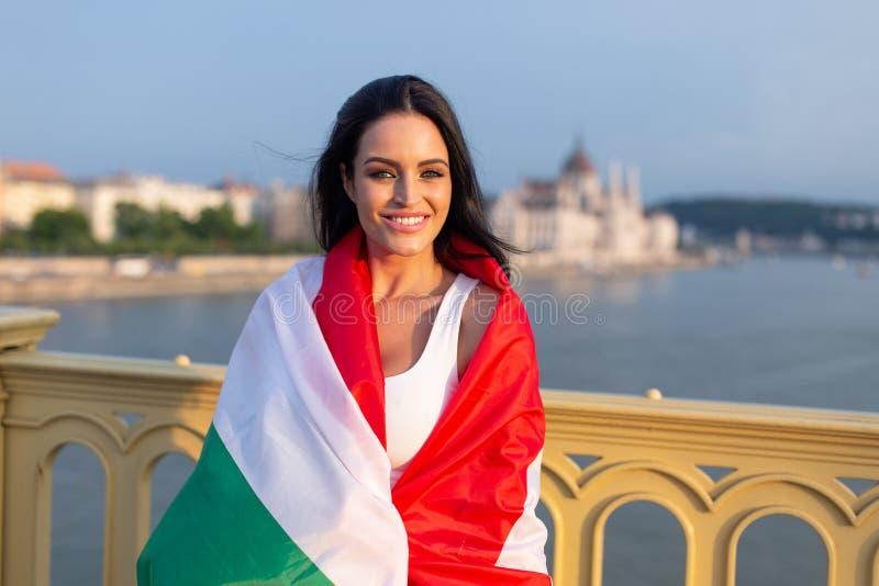 Szczęśliwa młoda kobieta zakrywająca hungarian flaga fotografia stock