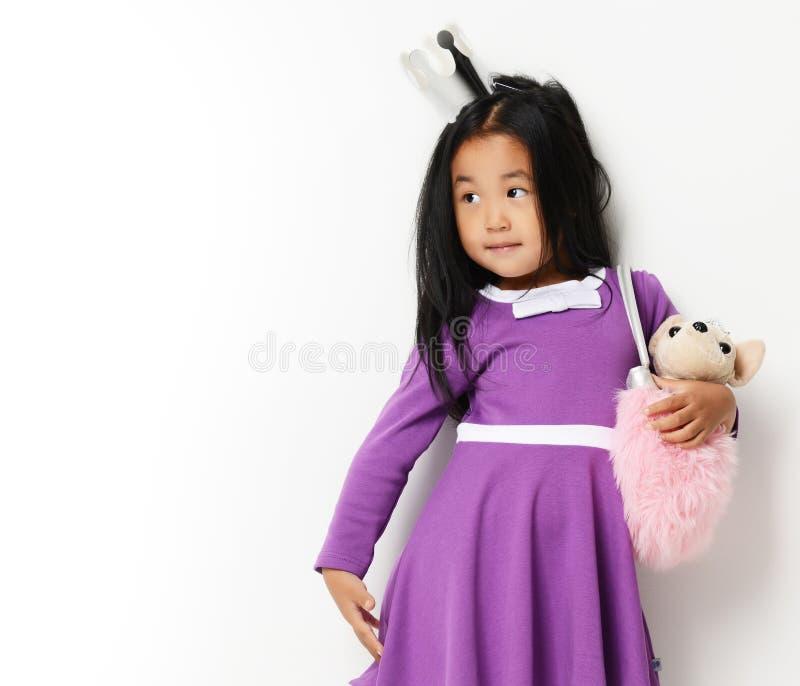 Szczęśliwa młoda mała azjatykcia dziecko dziewczyna przygotowywająca dla urodziny z małym psem w torbie patrzeje kąt obraz royalty free