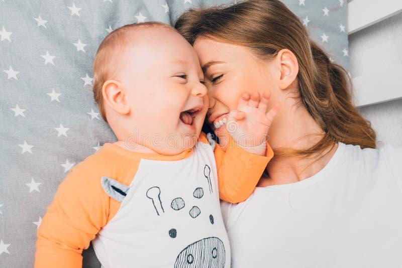 Szczęśliwa młoda matka i dziecko leżące na łóżku w domu obraz royalty free