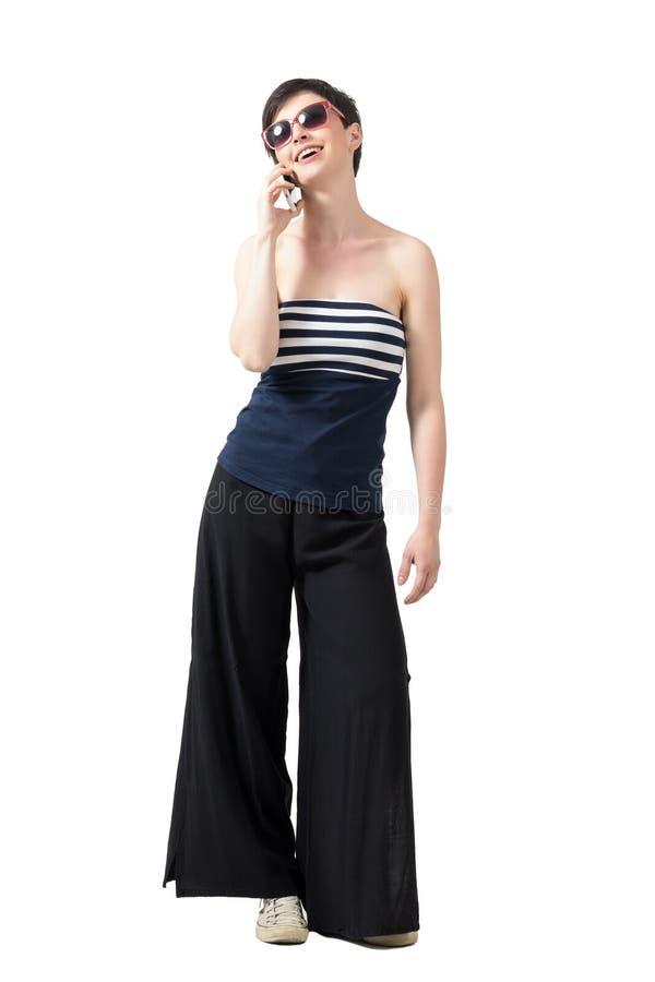 Szczęśliwa młoda modna kobieta opowiada na telefonu komórkowego ono uśmiecha się w ramię odgórnych jest ubranym okularach przeciw obrazy royalty free