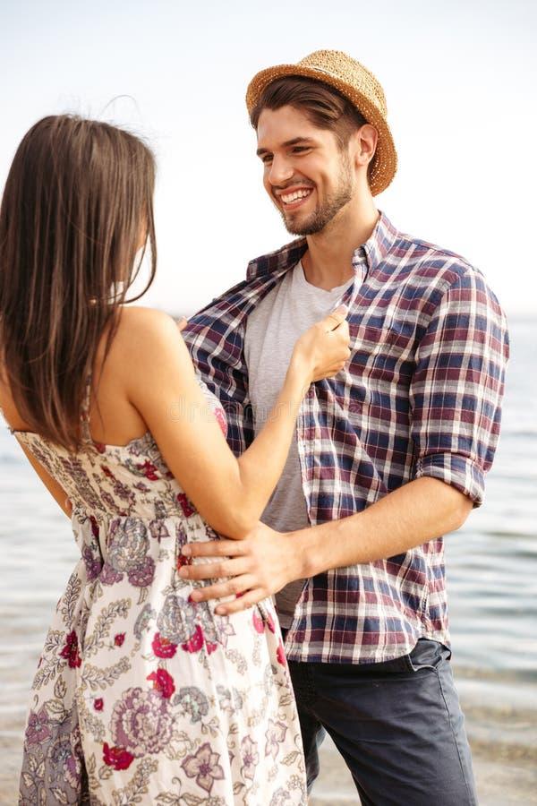 Szczęśliwa młoda modniś pary pozycja przy przytuleniem i plażą obraz royalty free