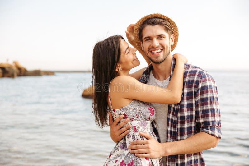 Szczęśliwa młoda modniś pary pozycja przy przytuleniem i plażą zdjęcie stock