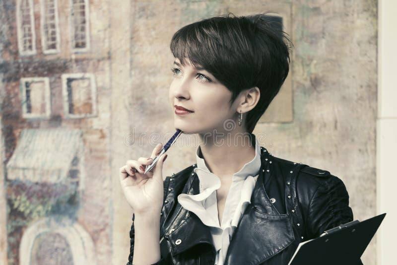 Szczęśliwa młoda mody biznesowa kobieta w skórzanej kurtce z schowkiem obraz stock