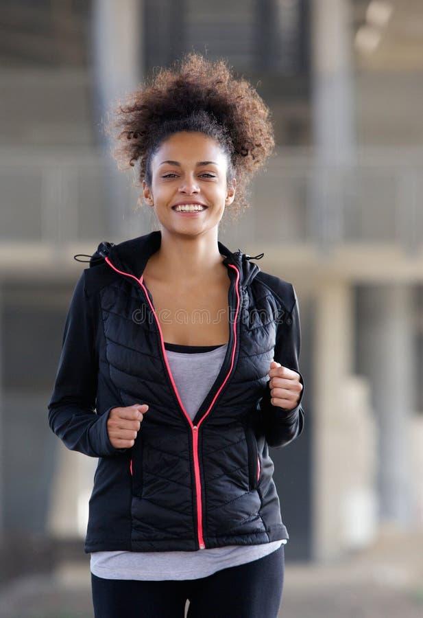 Szczęśliwa młoda murzynka biega outdoors obrazy stock