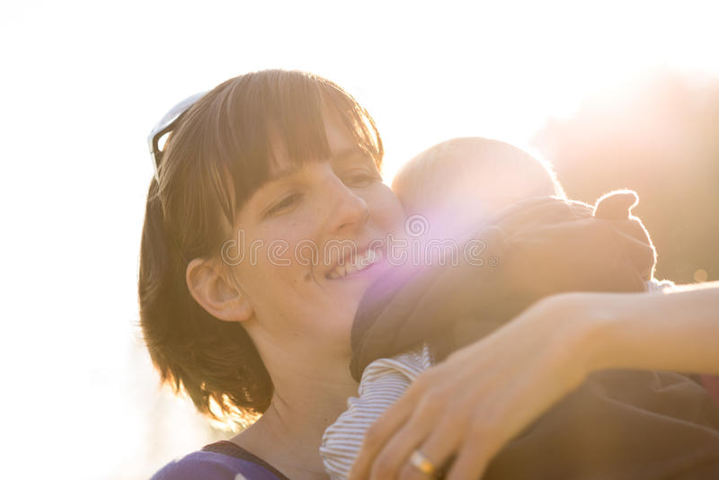 Szczęśliwa młoda ochronna matka czule cuddling jej chłopiec obrazy royalty free