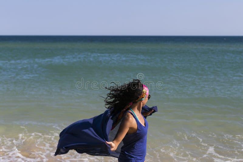 szczęśliwa młoda piękna kobieta bawić się z błękitną chustą przy plażą Zabawa, wiatr i styl życia, obraz stock