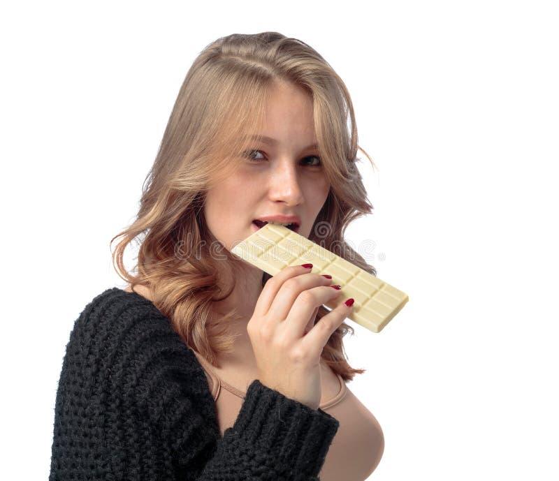 Szczęśliwa młoda piękna kobieta je białą czekoladę obrazy stock