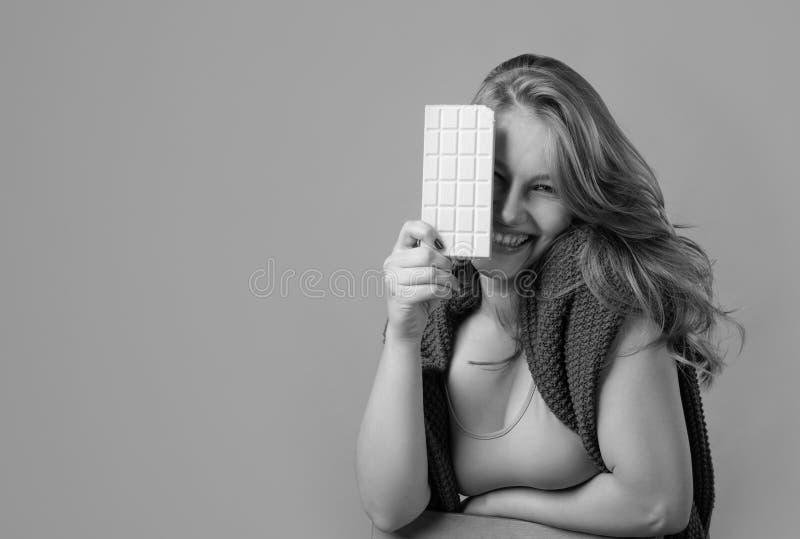 Szczęśliwa młoda piękna kobieta je białą czekoladę fotografia royalty free