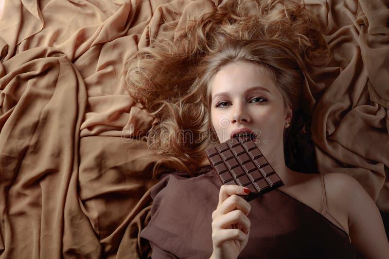 Szczęśliwa młoda piękna kobiety łasowania czekolada obraz stock