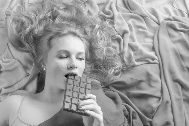 Szczęśliwa młoda piękna kobiety łasowania czekolada zdjęcia stock
