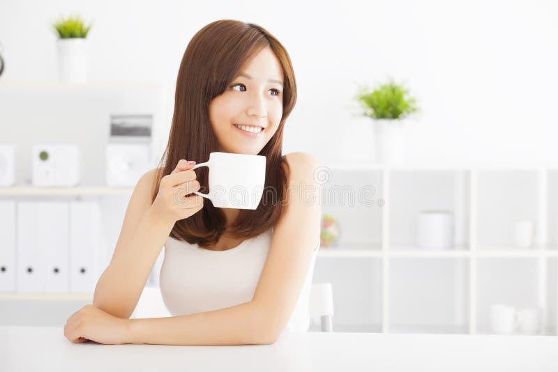 Szczęśliwa młoda pije kawa zdjęcia royalty free
