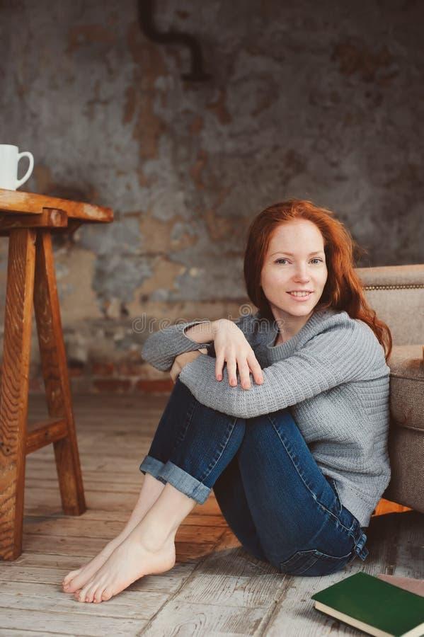 Szczęśliwa młoda readhead kobieta pije gorącą kawę lub herbaty w domu Spokojny i wygodny weekend w zimie obraz stock