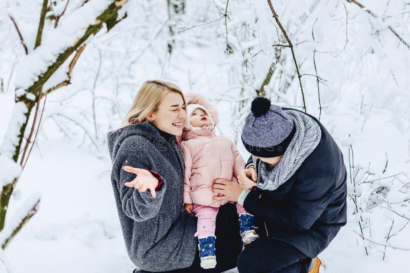 szczęśliwa młoda rodzina chodzi z dzieckiem na zimy ulicie, mama, tata, c zdjęcie royalty free