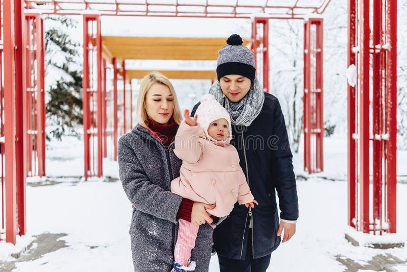 szczęśliwa młoda rodzina chodzi z dzieckiem na zimy ulicie, mama, tata, c zdjęcia royalty free