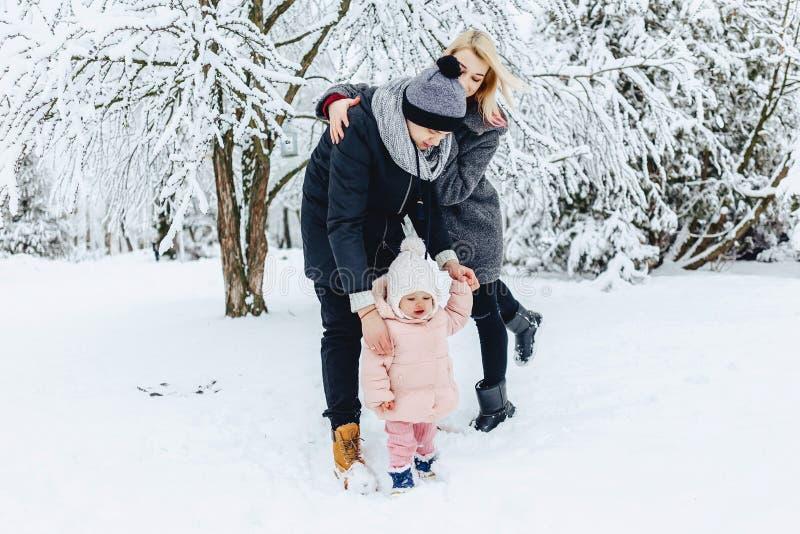 szczęśliwa młoda rodzina chodzi z dzieckiem na zimy ulicie, mama, tata, c zdjęcia stock