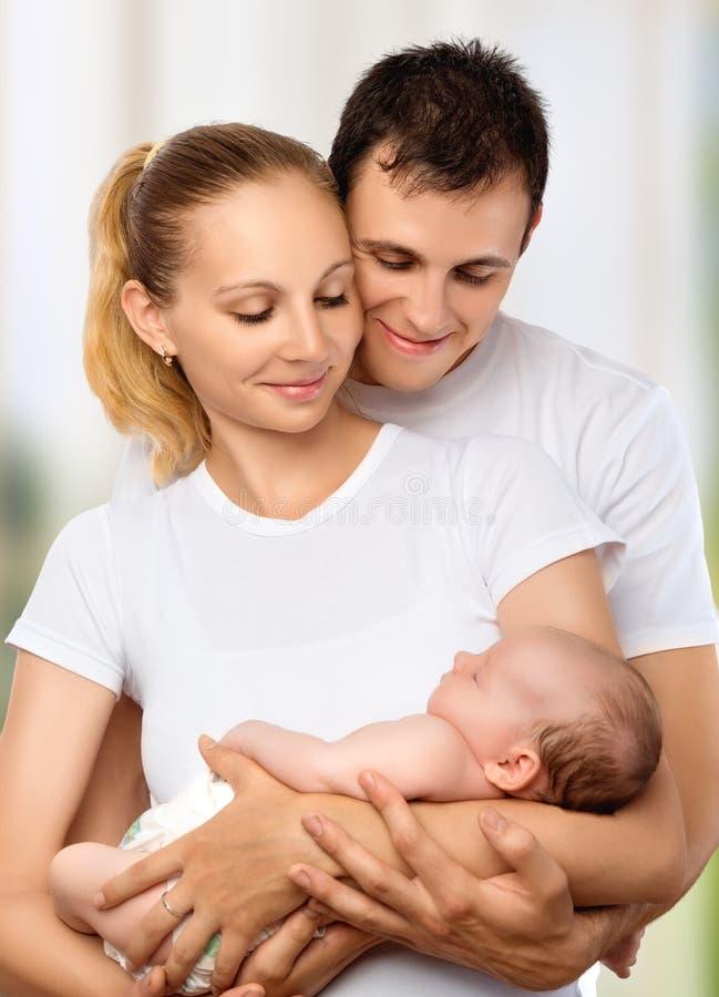 Szczęśliwa młoda rodzina matka, ojciec i nowonarodzony dziecko w ich a, zdjęcie royalty free