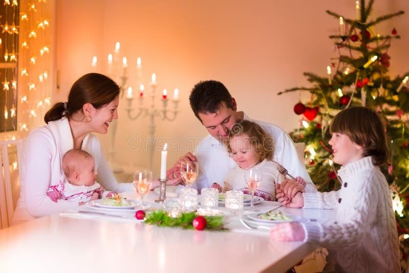 Szczęśliwa młoda rodzina przy Bożenarodzeniowym gościem restauracji zdjęcia stock