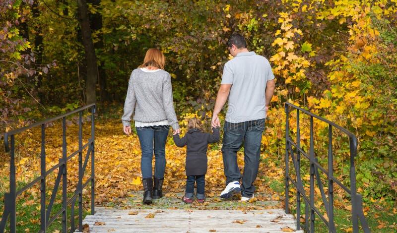 Szczęśliwa młoda rodzina w jesieni robi chodzącej wycieczce turysycznej zdjęcia royalty free