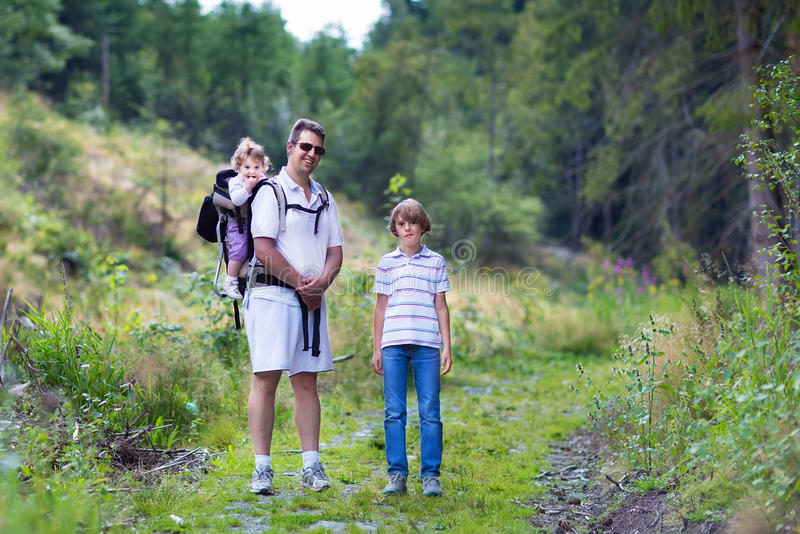 Szczęśliwa młoda rodzina wycieczkuje w pięknym jesień lesie obrazy stock