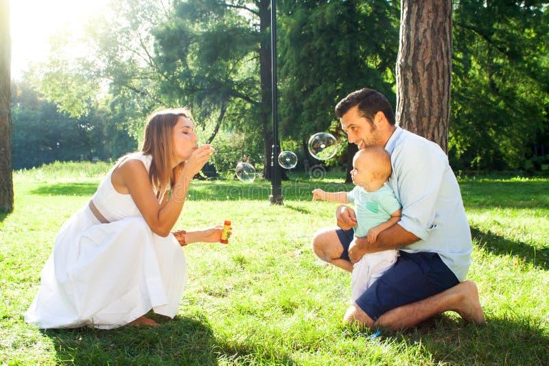 Szczęśliwa młoda rodzina wydaje czas plenerowego na lata daycouple zdjęcia royalty free