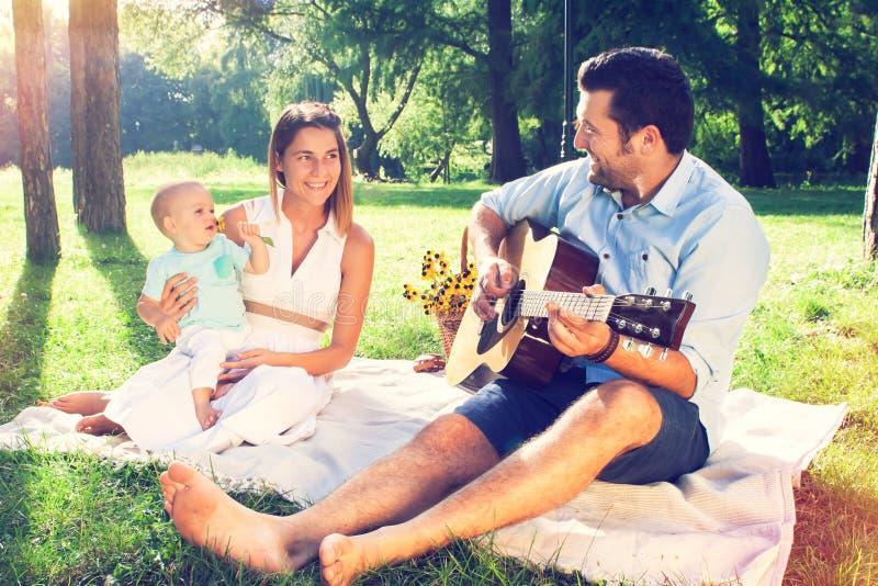 Szczęśliwa młoda rodzina wydaje czas plenerowego na letnim dniu fotografia stock
