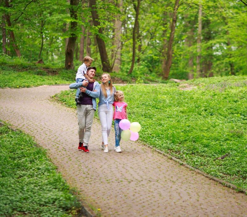 Szczęśliwa młoda rodzina z ich dwa dziećmi chodzi w lato lasu parku, rodzicielstwo wakacje z dzieciakami zdjęcie stock