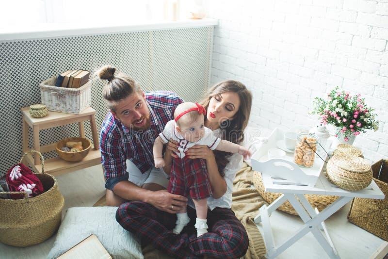Szczęśliwa młoda rodziny matka, ojciec i córka bawić się na dywanie w domu, obraz stock