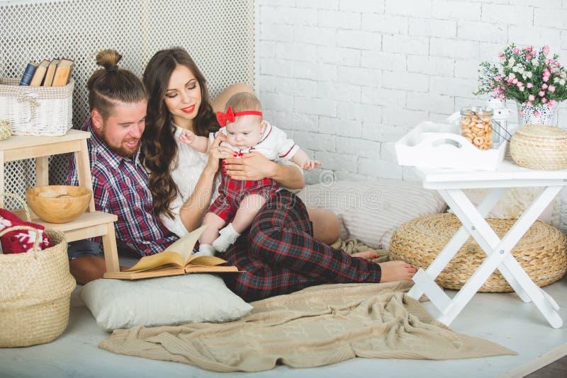 Szczęśliwa młoda rodziny matka, ojciec i córka bawić się na dywanie w domu, zdjęcie stock