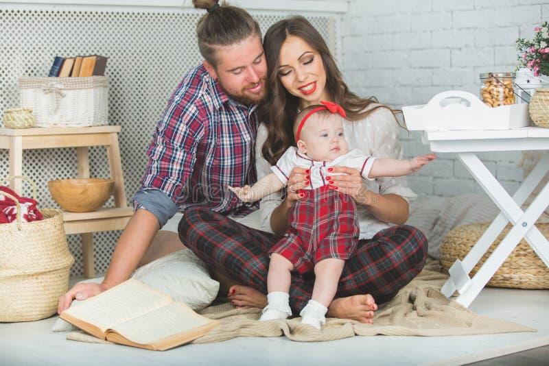 Szczęśliwa młoda rodziny matka, ojciec i córka bawić się na dywanie w domu, fotografia stock