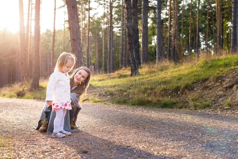 Szczęśliwa młoda samotna matka bierze spacer w parku z jej berbeć córką Rodzinny uśmiechać się zabawę i mieć obraz stock