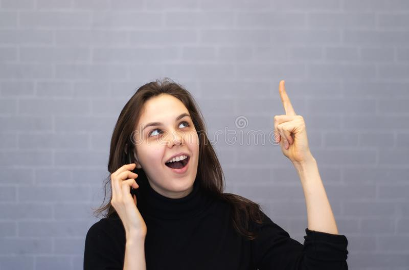 Szczęśliwa młoda uśmiechnięta kobieta opowiada na telefonie i wskazuje palec na kopii przestrzeni obraz royalty free