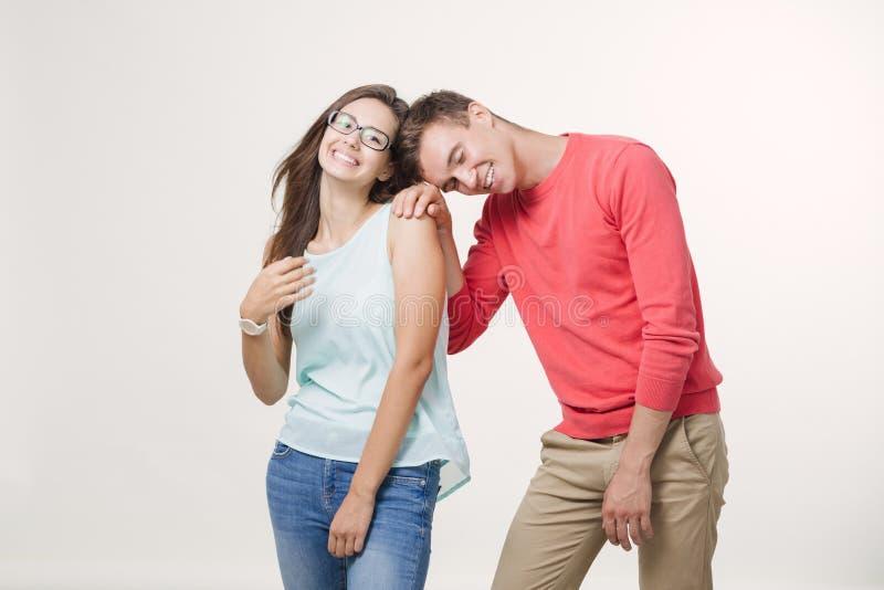 Szczęśliwa młoda urocza para stoi wpólnie i śmia się (4-5 rok) Nad biały tłem pracowniany strzał Przyjaźń, miłość i zdjęcia royalty free