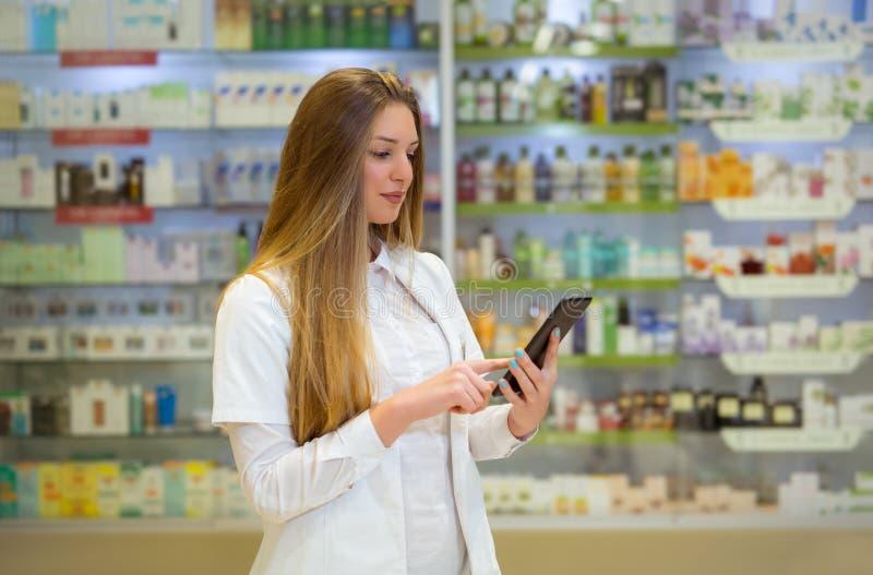 Szczęśliwa młodej kobiety farmaceuta nad apteki tłem zdjęcie royalty free
