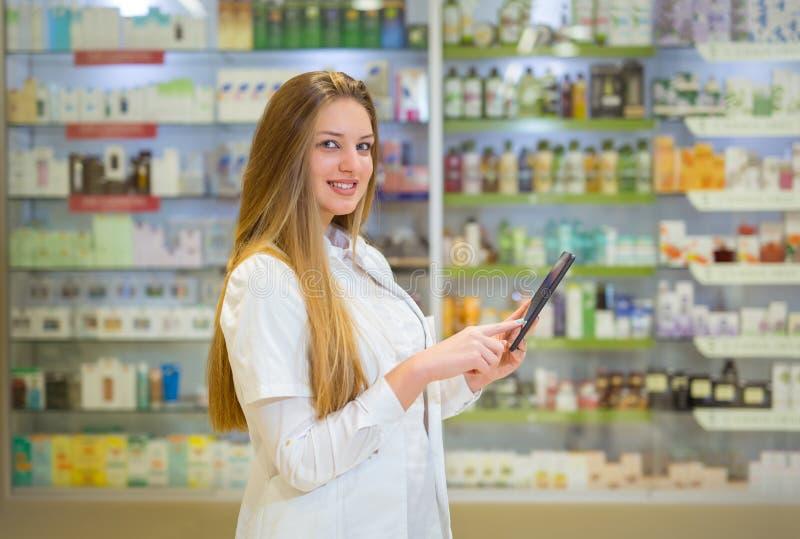 Szczęśliwa młodej kobiety farmaceuta nad apteki tłem zdjęcie stock
