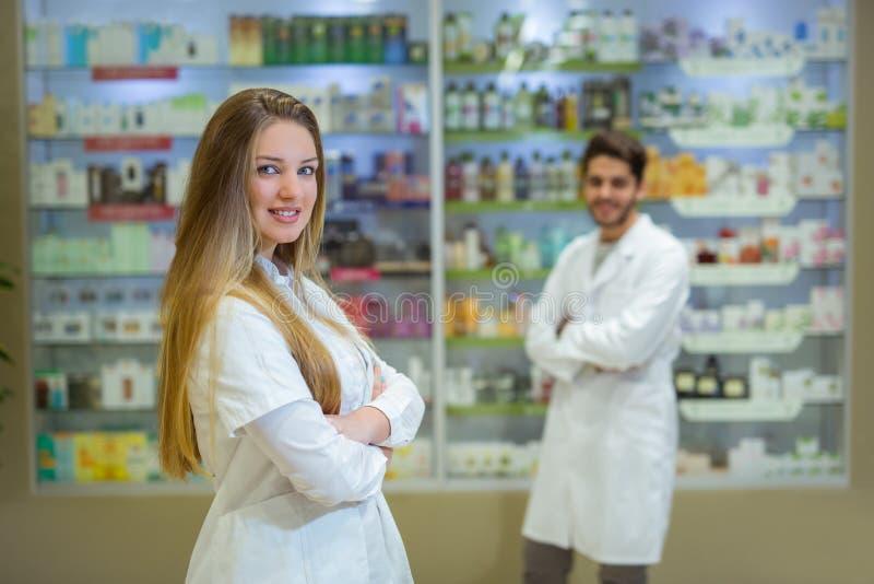 Szczęśliwa młodej kobiety farmaceuta nad apteki tłem obraz stock
